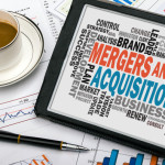mergers and acquisitions concept with business word cloud handwritten on tablet pc
